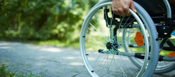 Close-up of male hand on wheel of wheelchair during walk in park